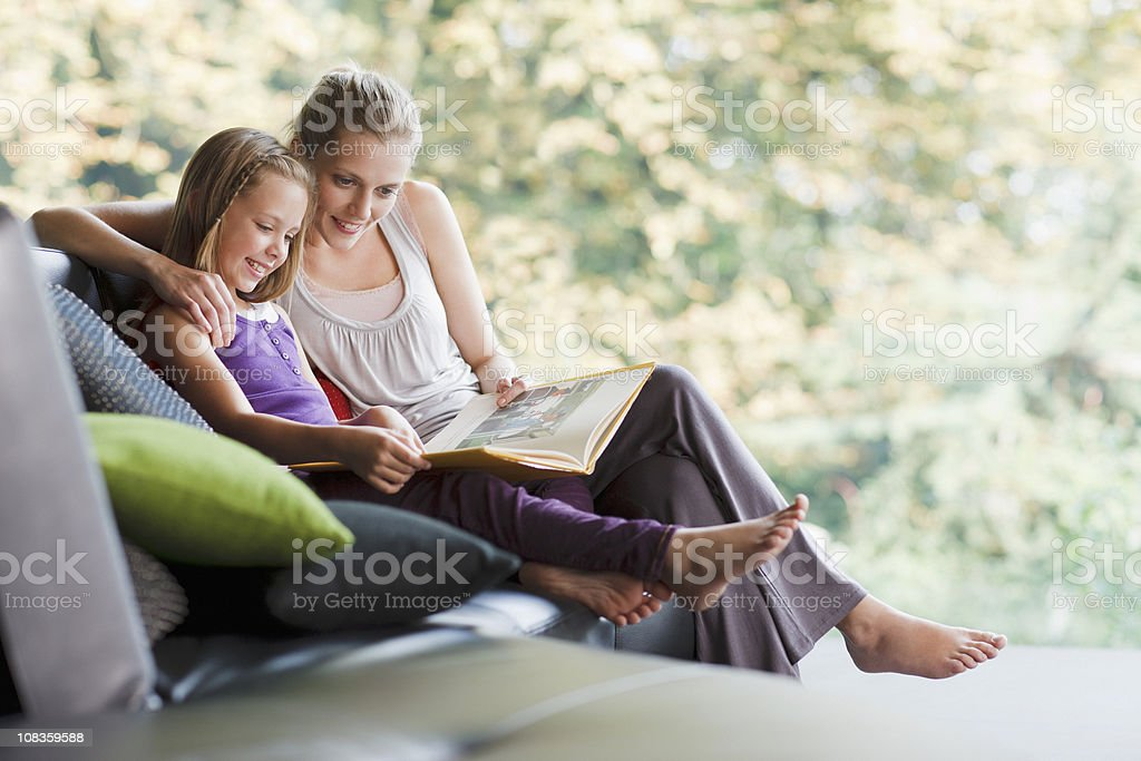 Mother and daughter reading storybook stock photo