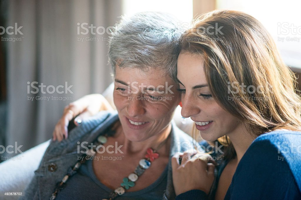 Mother and daughter reading together stock photo
