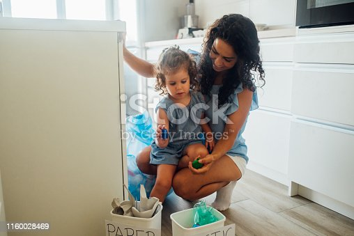 Happy young woman teaching her daughter to recycle