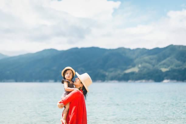 Mãe e filha relaxadas na praia - foto de acervo