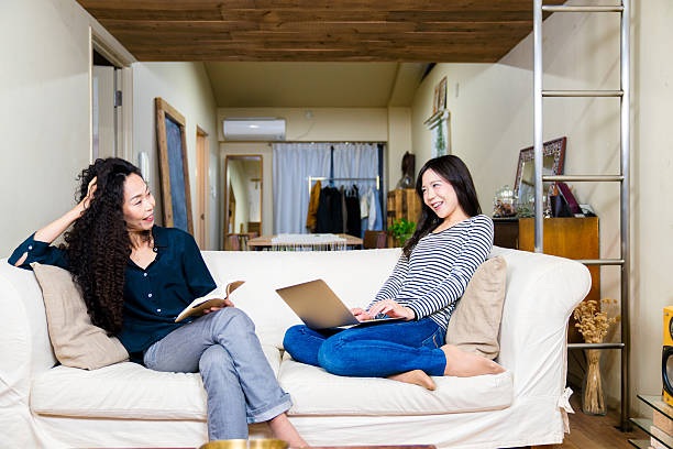 Mother and daughter relaxing at home on the sofa. stock photo