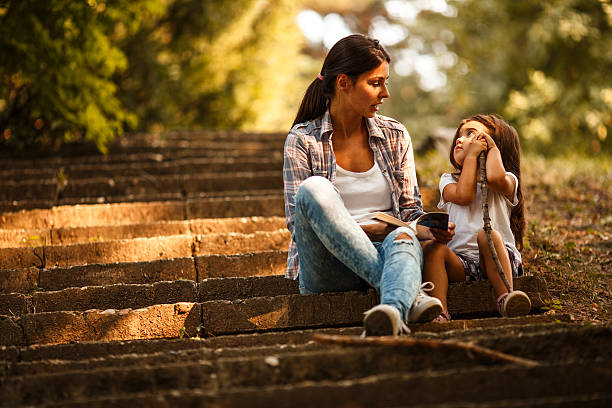 Mother and daughter relaxing in park. stock photo
