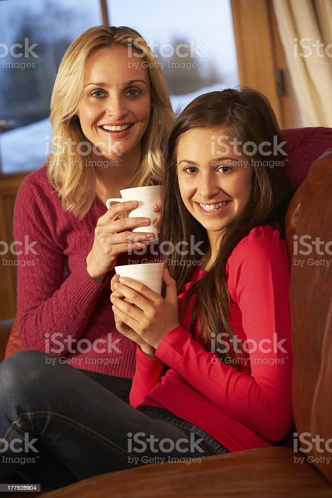 Mother And Daughter Relaxing On Sofa Together With Hot Drink royalty-free stock photo