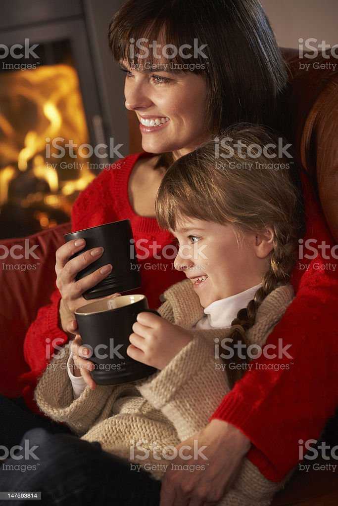 Mother And Daughter Relaxing With Hot Drink By Fire royalty-free stock photo