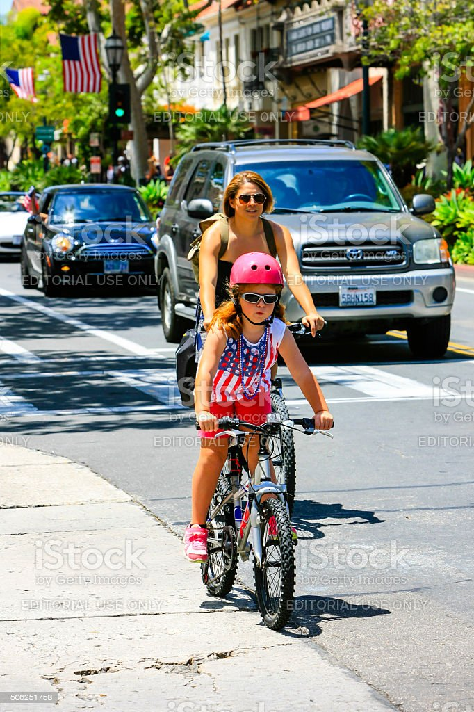 Mother and daughter riding bicycles together stock photo