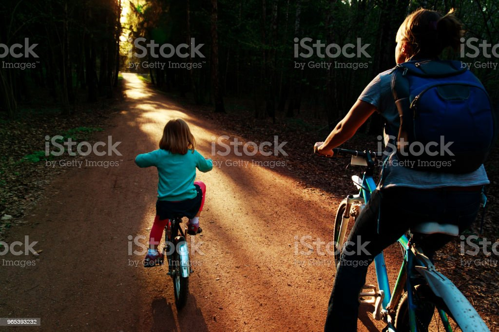 mother and daughter riding bikes in sunset nature royalty-free stock photo