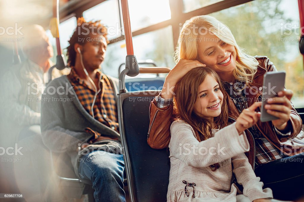 Mother and daughter riding in a bus stock photo
