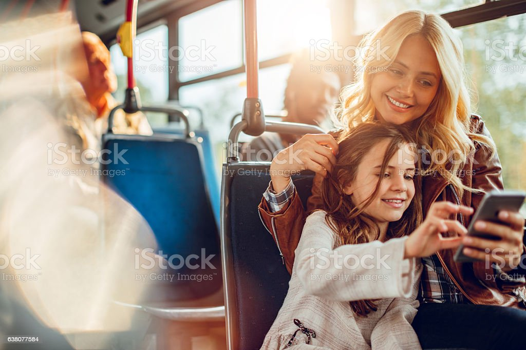 Mother and daughter riding in a bus - Photo