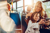 Mother and daughter riding in a bus