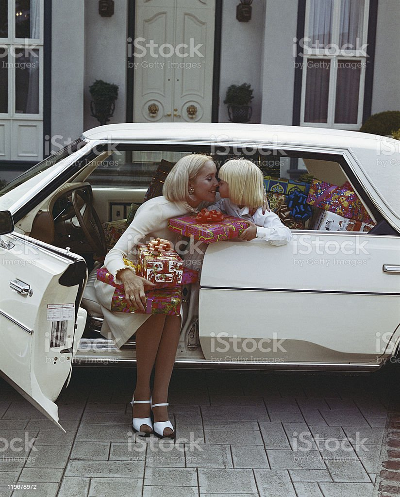 Mother and daughter rubbing noses in car with gifts box stock photo