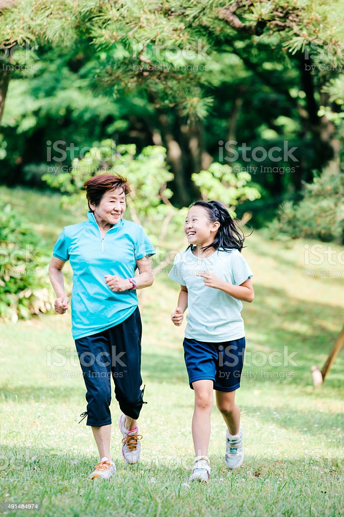 Mother and daughter running in a Tokyo park, Tokyo, Japan stock photo