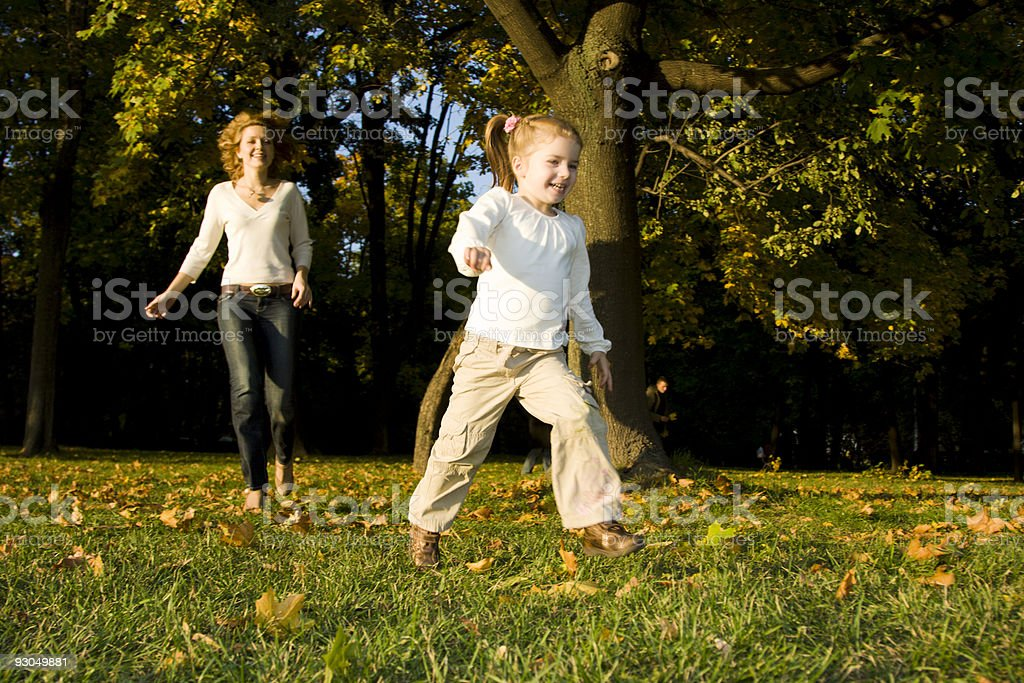 Mother and daughter running in autumn park royalty-free stock photo