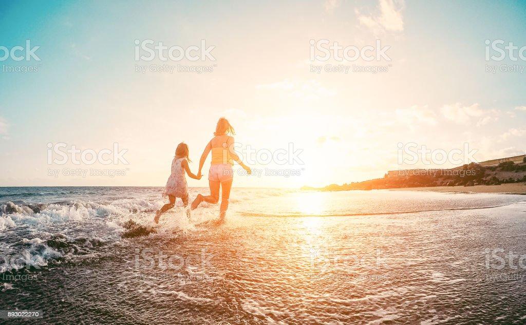 Mutter und Tochter läuft innerhalb des Wassers am tropischen Strand - Mama spielen mit ihrem Kind im Urlaub direkt am Meer - Familie Lebensstil und Liebe Konzept - Fokus auf Silhouetten – Foto