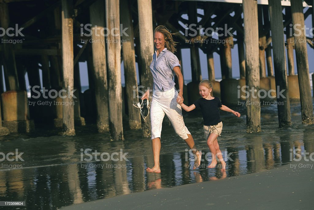 Mother and Daughter running on the beach royalty-free stock photo
