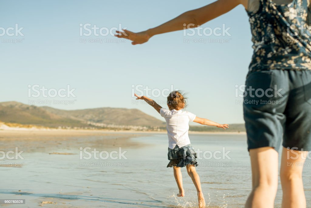 Mother and daughter running on the beach with their arms outstretched as though they're flying stock photo