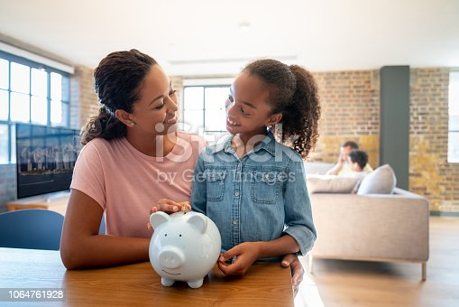 Portrait of a happy African American mother and daughter saving money in a piggybank and smiling - home finances concepts