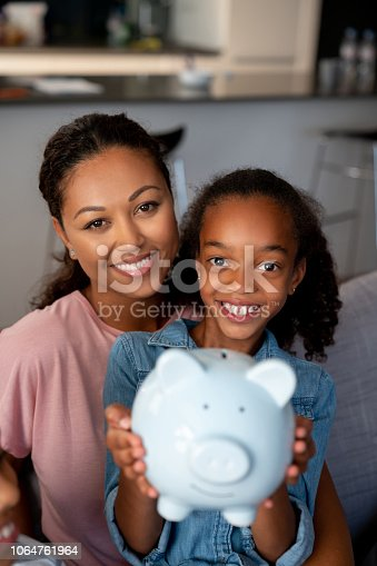 Portrait of a happy African American mother and daughter saving money in a piggybank and looking at the camera smiling - home finances concepts