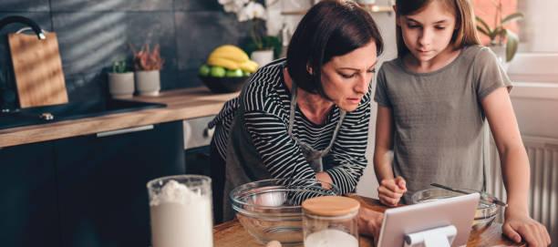Mutter und Tochter suchen Apfelkuchen Rezept auf dem tablet – Foto