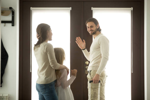 mother and daughter seeing off father leaving, waving hands goodbye - mom spying stock photos and pictures