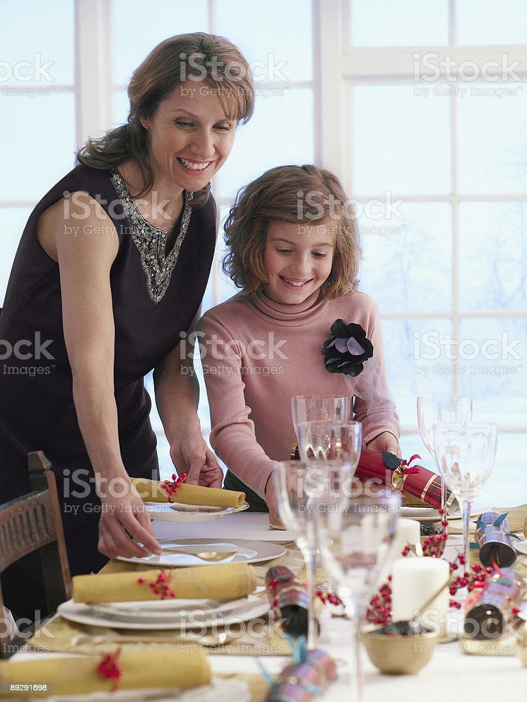 Mother and daughter setting table for Christmas dinner stock photo