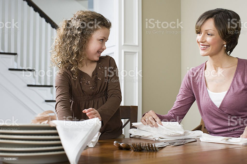 Mother and daughter setting the table royalty-free stock photo