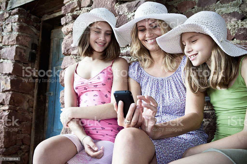 Mother and daughter sharing smartphone stock photo