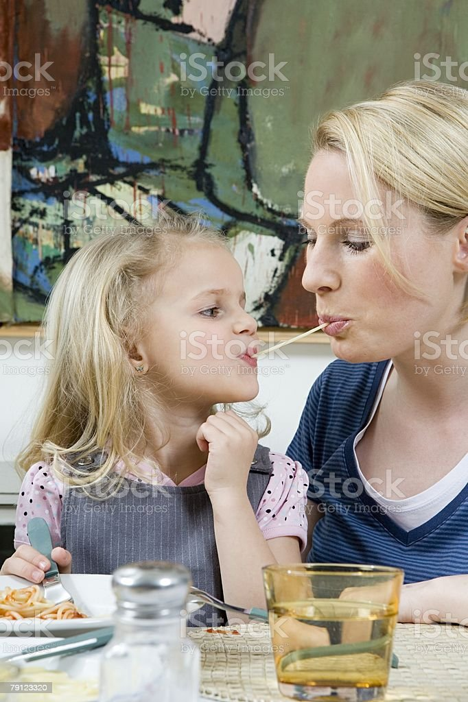 Mother and daughter sharing spaghetti royalty-free 스톡 사진