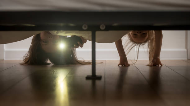mother and daughter shine a flashlight looking under the bed - abaixo imagens e fotografias de stock