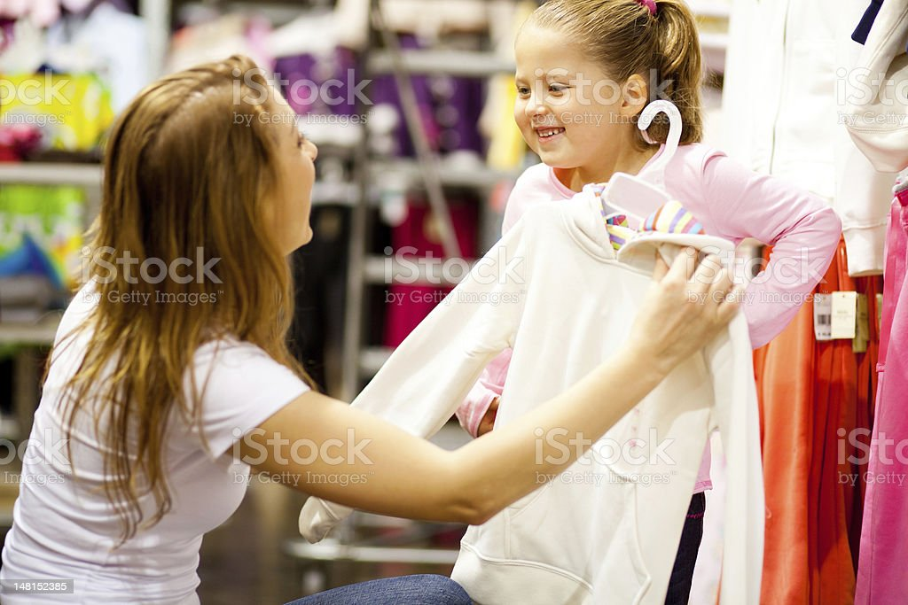 mother and daughter shopping for clothes stock photo