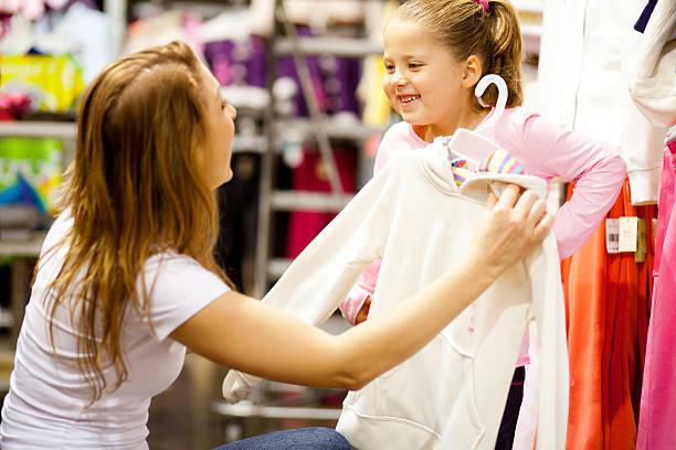 mother and daughter shopping for clothes - kledingwinkel stockfoto's en -beelden
