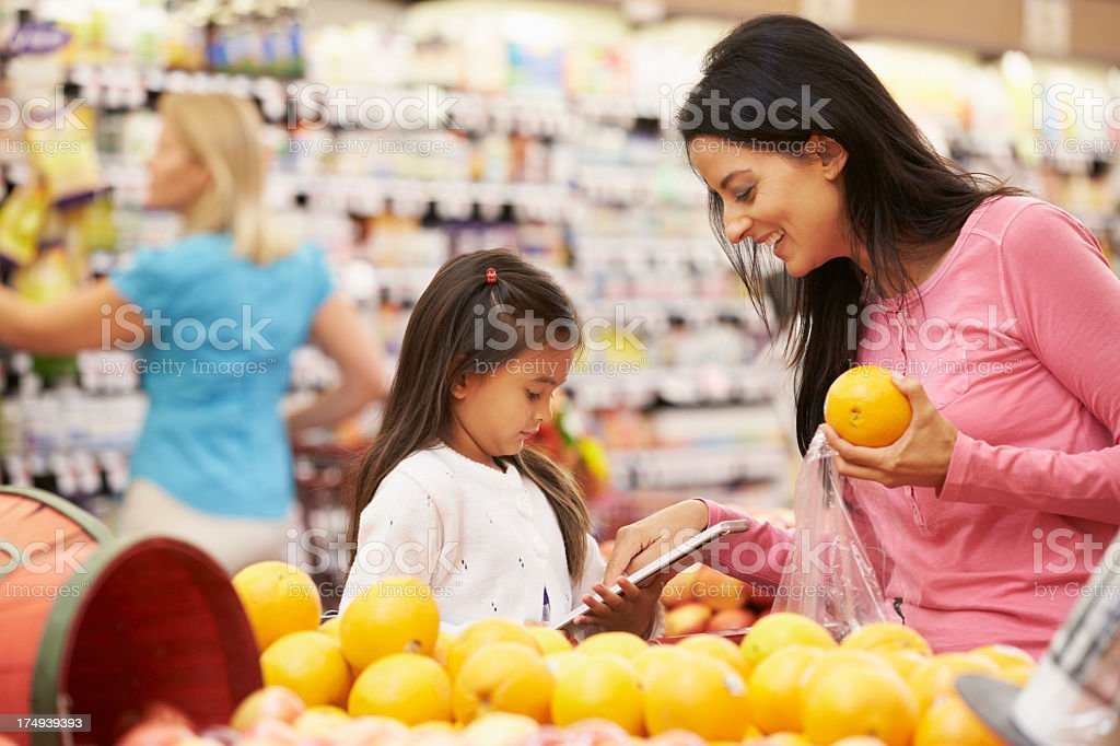 A mother and daughter shopping for oranges at the market stock photo