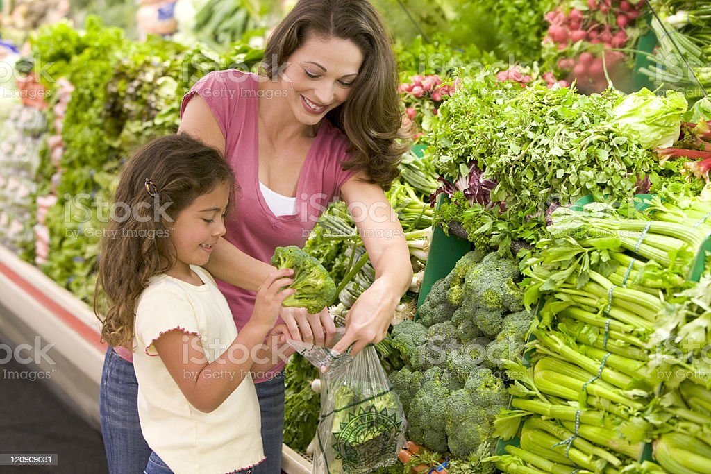 Mother and daughter shopping for produce stock photo