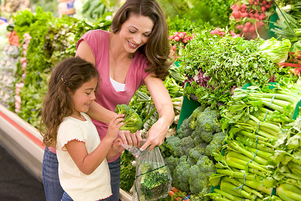 Mother and daughter shopping for produce Mother and daughter shopping for produce in supermarket produce aisle stock pictures, royalty-free photos & images