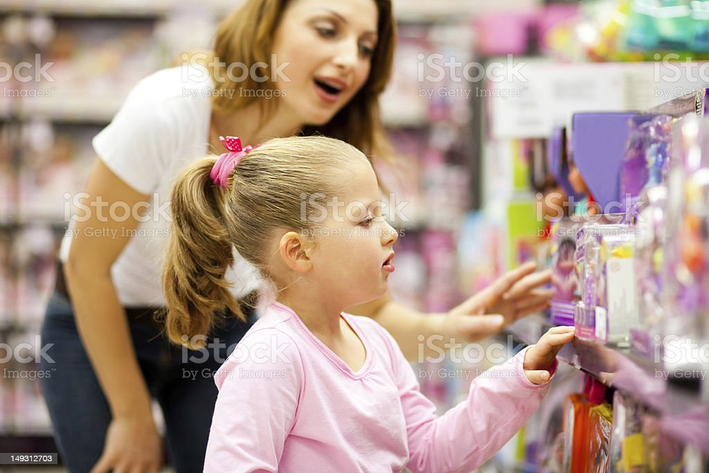mother and daughter shopping for toys stock photo