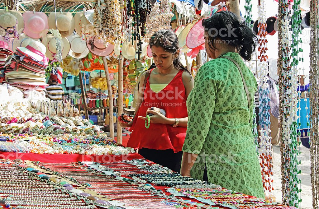 Mother and Daughter Shopping in Flea Market Mother and teenage daughter looking for fancy jewelry and accessories in a flea market in Goa, India Adult Stock Photo