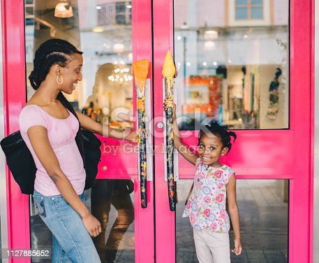 Little girl and her mother hold the handles of a retail shop about to go in, maybe on a mother daughter bonding trip doing some shopping. Candid cute moment between mother and daughter. Family is African American and child is 4 years old. Having fun and browsing shops