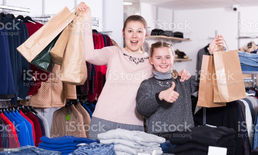 Mother and daughter showing thumbs up in clothes shop royalty-free stock photo