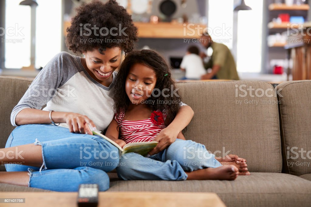 Mother And Daughter Sit On Sofa In Lounge Reading Book Together - fotografia de stock