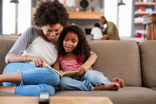 mother and daughter sit on sofa in lounge reading book together - mother stock photos and pictures