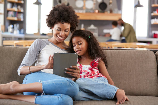 Mother And Daughter Sit On Sofa In Lounge Using Digital Tablet stock photo