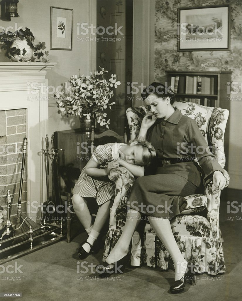 Mother and daughter sitting in living room 免版稅 stock photo