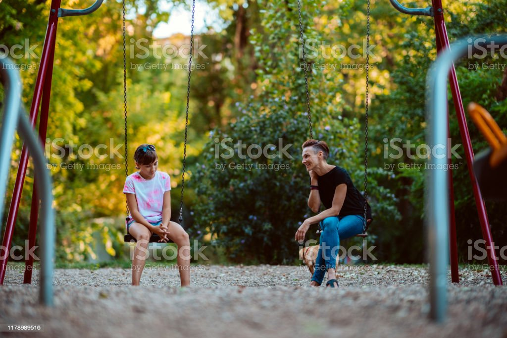 Mother and daughter sitting on a swing and having serious conversation Mother and daughter sitting outdoor on a swing at the playground and having serious conversation 12-13 Years Stock Photo