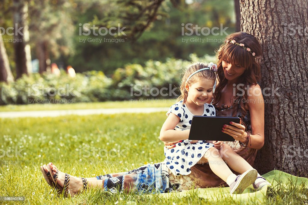 Mother and daughter sitting on grass using digital tablet. royalty-free stock photo