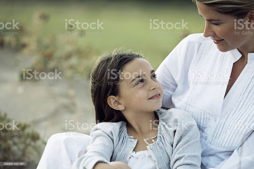 Mother and daughter (6-8) sitting on grassy dunes, close-up royalty-free stock photo