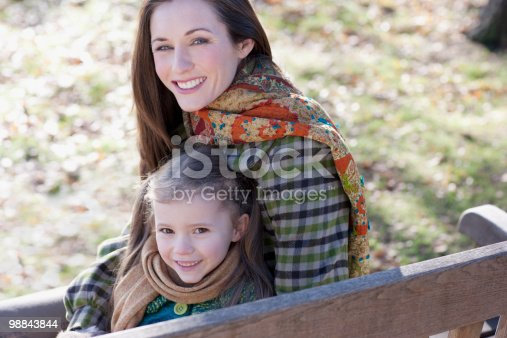 Mother And Daughter Sitting On Park Bench Stock Photo & More Pictures of 30-34 Years