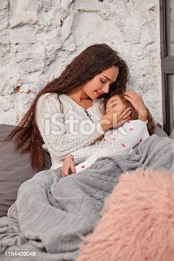 Mother and daughter sitting on sill near window in room. The daughter sleeping on mother's hands