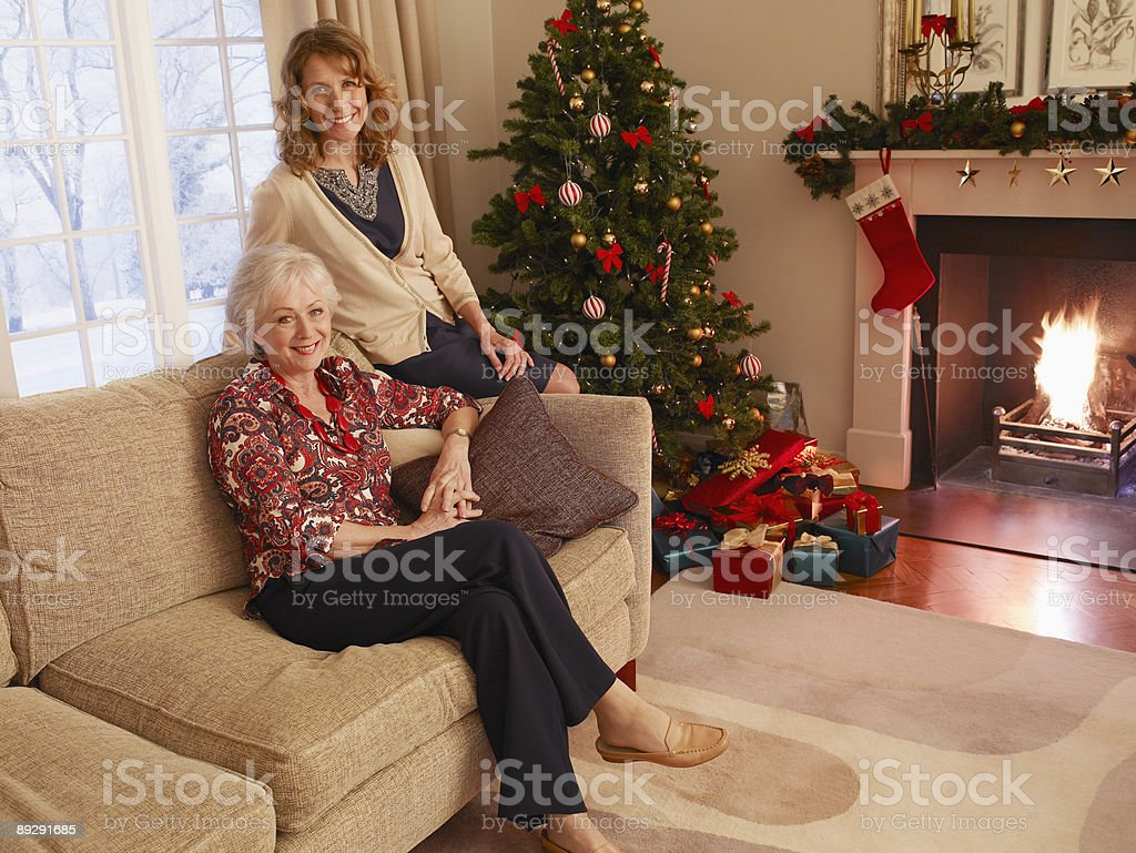Mother and daughter sitting on sofa near Christmas tree royalty-free stock photo