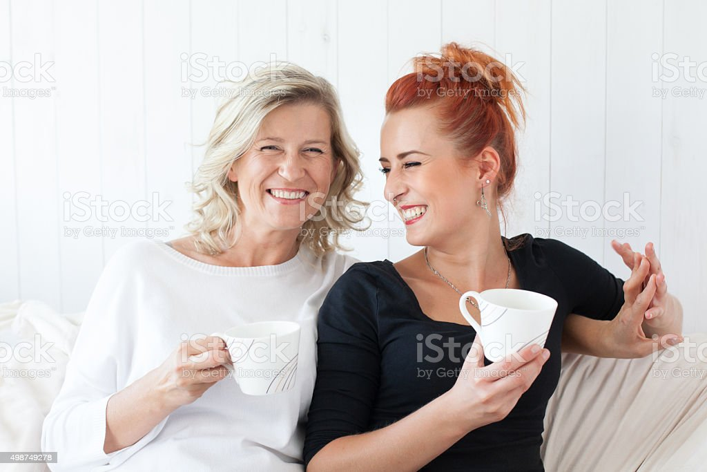 mother and daughter sitting on the sofa at home stock photo