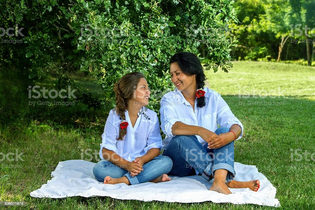 mother and daughter sitting under an oak tree stock photo