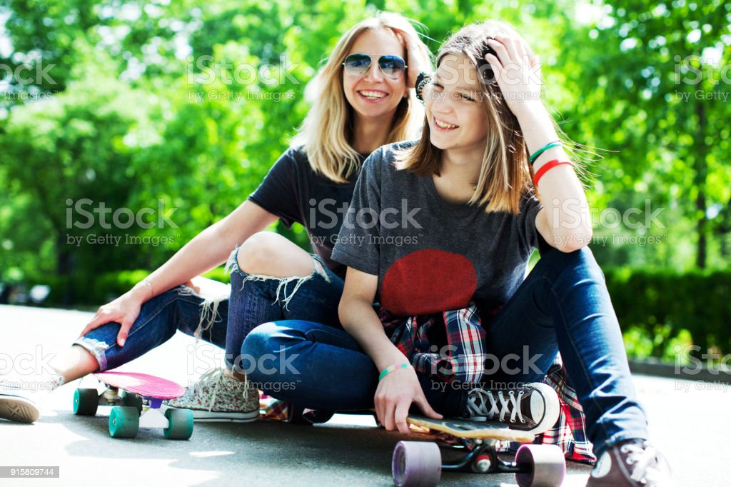 Mother and daughter skateboarding stock photo